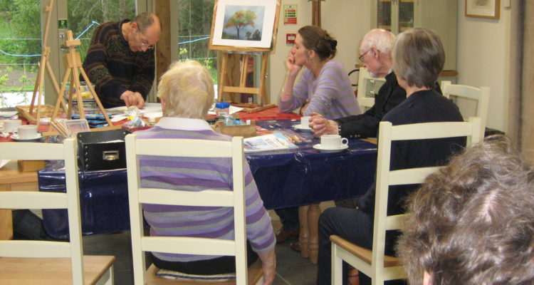 members around table at the botanic cottage at art group