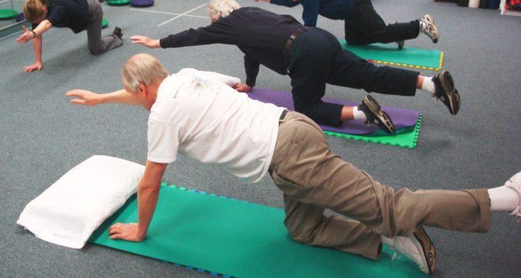 group gentle exercising on floor mats