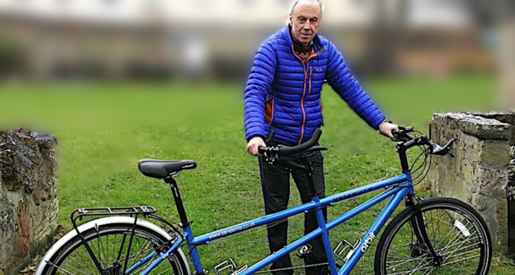 man standing beside tandem bicycle